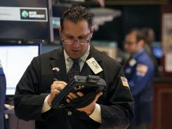Trader Edward Curran works on the floor of the New York Stock Exchange July 31, 2012.
