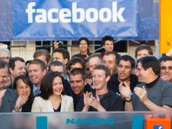 Facebook founder Mark Zuckerberg, center, applauds at the opening bell of the Nasdaq stock market from headquarters in Menlo Park, Calif. on the company's first day of trading on May 18, 2012.