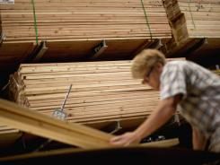 Michael McGehee loads lumber onto a cart while shopping at Lowe's store in Atlanta.