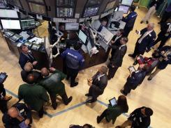 Traders and floor officials gather at a post on the floor of the New York Stock Exchange shortly after the beginning of trading, Aug. 1, 2012.