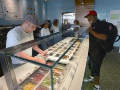 Legil Moody, right, watches as Chris Morse adds toppings to his Greek yogurt at Pinkberry's Dupont Circle store in Washington, D.C. on July 25, 2012.