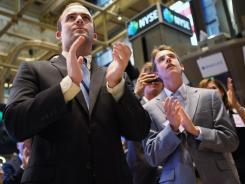 Guests applaud Friday at the closing bell of the New York Stock Exchange, where stocks surged following a surprisingly strong monthly jobs report.