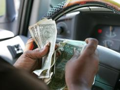 A consumer counting her cash in her car.