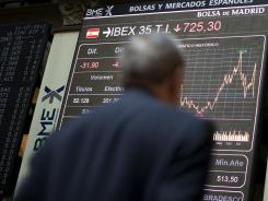 A trader looks at a display board showing information on the Madrid Stock Exchange on July 31, 2012.