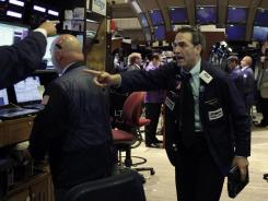 Trader Gregory Rowe, right, works on the floor of the New York Stock Exchange in this July 26, 2012, photo.