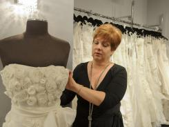 Linda Morado, owner of Le Dress in Atlanta, straightens a bridal gown at her shop.