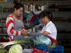 A woman pays for vegetables at a store in Changping, on the outskirt of Beijing, Aug. 9, 2012.