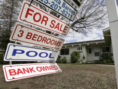 A foreclosure sign blows in the wind in this file photo. Lenders increasingly are trying to avoid repossessing homes.