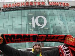 Winner: A Manchester United fan holds up a scarf celebrating Manchester United's 19  titles..