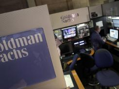A trader works in the Goldman Sachs booth on the floor of the New York Stock Exchange in this March photo. The Justice Department said it won't prosecute Goldman Sachs or its employees in a financial fraud probe.