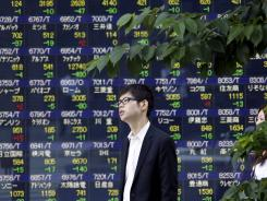 A man stands in front of the stock price display of a securities firm in Tokyo July 9.