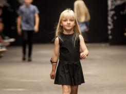 Children wear clothes by the designer company New General during a runway show Friday at Copenhagen Fashion Week.