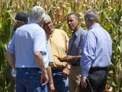 President Obama and Agriculture Secretary Tom Vilsack, right, inspect drought damaged corn Monday at a Missouri Valley, Iowa, farm.