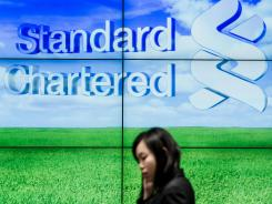 A woman walks past a display board outside a branch of the Standard Chartered Bank in Hong Kong on Aug. 7, 2012.