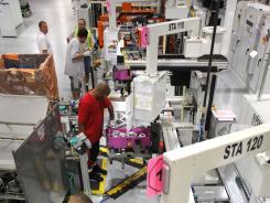Workers stand on the line during the production of the new hybrid transmission for Ford's five new electric and hybrid vehicles at Ford Motor Company's Van Dyke Transmission Plant August 2, 2012 in Sterling Heights, Michigan.
