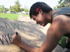 Turtle Eng of Harrisburg, Pa., draws a protest sign Aug. 13 in Helena, Mont.