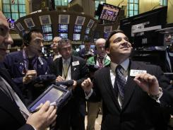 Stock specialist Paul Cosentino, right, directs trading on the floor of the New York Stock Exchange on March 21, 2012.