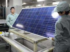 Workers assemble solar panels by hand on the factory floor of Chinese company Suntech in the eastern Chinese city of Wuxi on Feb. 27, 2012.