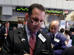 Trader Edward Curran, left, works on the floor of the New York Stock Exchange Aug. 15, 2012.