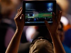A fan uses an Apple iPad to photograph the game between the St. Louis Cardinals and the Colorado Rockies at Coors Field on Aug. 1, 2012, in Denver, Colo.