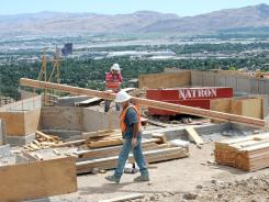 Kary Kesner carries lumber for a new home under construction at the top of Ridgeview Drive in southwest Reno, Nev., in June 2012.