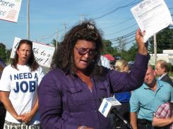Lynn Tipton, front, president of a local union and a worker at the Rhode Island Department of Labor and Training, protesting layoffs at the department in July 2012, in Cranston,