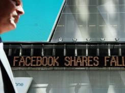 A news ticker announces the falling share price Thursday of Facebook in New York City's Times Square.