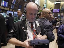 Trader Kevin Walsh, center, works on the floor of the New York Stock Exchange in August 2012.