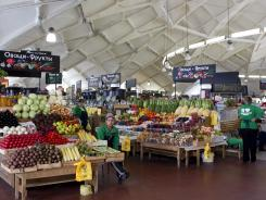 Vendors wait for customers at a Moscow market, Aug. 22, 2012.