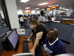 Linda Robinson, left, and her husband Timothy look for work online at WorkForce One, Aug. 1, 2012, in Hollywood, Fla.