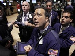 Robert Vella, center, works with fellow traders on the floor of the New York Stock Exchange Thursday, Aug. 9, 2012. Stocks are inching higher in early trading after the U.S. government reported that claims for unemployment benefits fell last week. (AP Photo/Richard Drew) ORG XMIT: NYRD102