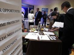 Job seekers visit a Primerica booth at a job fair in San Jose, Calif., in July 2012.
