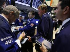 Specialist Joseph Mastrolia, center, works with traders on the floor of the New York Stock Exchange on Aug. 15, 2012.