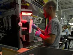 Machine operator Ed Snyder works in cell assembly line at General Electric's battery plant in Schenectady, N.Y., in July 2012.