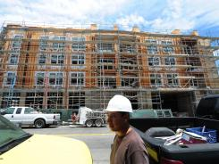 A construction worker walks past a block of new homes under construction and for sale in Alhambra, east of downtown Los Angeles on July 18, 2012.