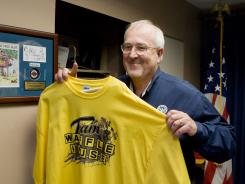 Craig Fugate, Federal Emergency Management Agency administrator, holds up a Team Waffle House shirt in his office in this file photo.