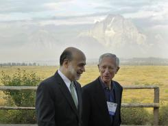 With the Teton Mountains behind them, Federal Reserve Chair Ben Bernanke, left, and Bank of Israel Gov. Stanley Fischer walk together outside of the Jackson Hole Economic Symposium, Aug. 31, 2012, at Jackson Hole, Wyo.