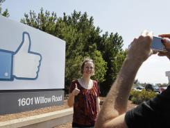 A German tourist poses for pictures outside Facebook headquarters in Menlo Park, Calif., Aug. 17, 2012.