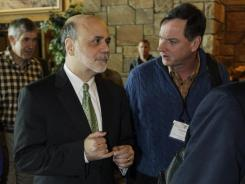 Fed Chairman Ben Bernanke, left, talks with Charles Evans of the Chicago Federal Reserve Bank at the Jackson Hole Economic Symposium on Friday.