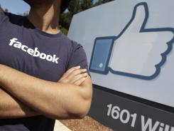A Facebook worker waits for friends to arrive outside of Facebook headquarters in Menlo Park, Calif., Aug. 17, 2012.