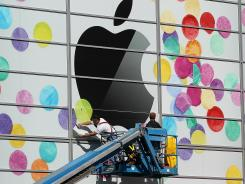 Workers apply the Apple logo outside a San Francisco building prior to a 2001 company event.