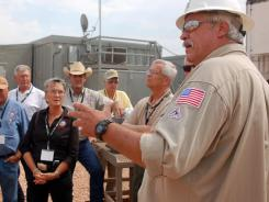 A Hess spokesman explains the oil-drilling process to lawmakers from North and South Dakota near Tioga, N.D. The oil boom has helped employment in both states.