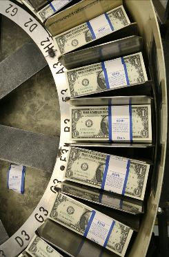 Stacks of dollar bills pass through a machine at the Bureau of Engraving and Printing in this file photo.