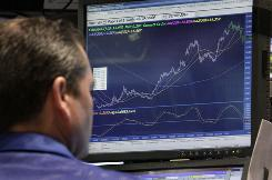Specialist Kristian Loughlin works at his post on the floor of the New York Stock Exchange in this file photo from Feb. 9, 2010.