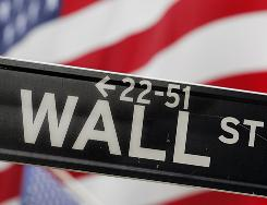 A Wall Street street sign is seen in front of flags at the New York Stock Exchange in this file photo.