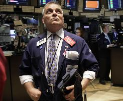 Trader Albert Young watches the board from the floor of the New York Stock Exchange as stocks rallied Friday, Oct. 8, 2010.