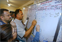 Iraqi stockbrokers write the prices of stocks on a board at the Iraq Stock Exchange in Baghdad on April 30. 