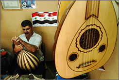 Iraqi lute maker Ahmed al-Abdali works in a shop in Baghdad on April 18. The instrument is used in traditional Middle Eastern music.