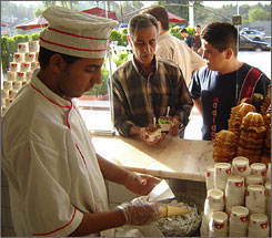 Ahmed Riyadh, left, serves ice cream cups and sundaes at the Hassan ice cream shop in Baghdad. Ice cream vendors such as the Hassan shop expect to do a brisk business as temperatures climb during summer.