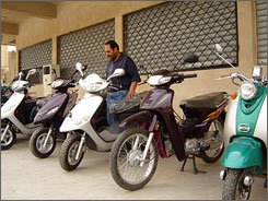Salam Kadhem of Baghdad reviews the scooters on his company's sidewalk in Arasat Street.